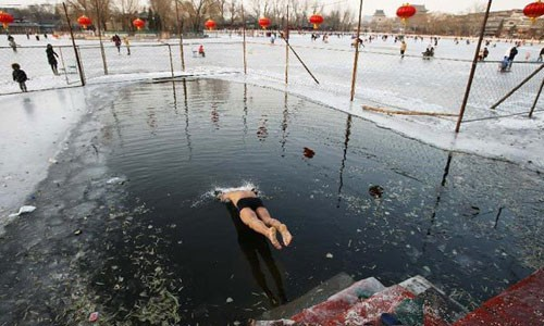 A winter swimmer jumps into the icy water of the frozen Shichahai lake in Beijing, capital of China, December 22, 2012. Temperatures in Beijing could plunge to the lowest in almost three decades over the weekend, weather forecasters said Saturday. Photo: Xinhua