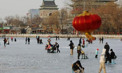 People enjoy themselves on the frozen Shichahai lake in Beijing, capital of China,December 22, 2012. Temperatures in Beijing could plunge to the lowest in almost three decades over the weekend, weather forecasters said Saturday.